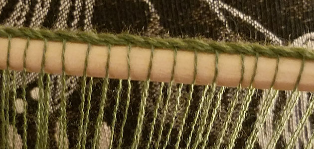 Plying a cord around the warp threads creates even spacing.